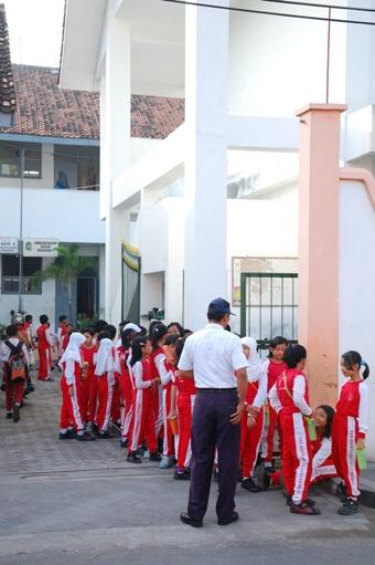 pak satpam mengatur barisan siswa SD ini menuju lapangan Karang